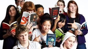group of teenagers all holding books up in front of the camera